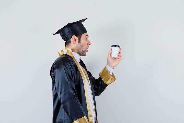 Varón joven mirando una taza de café en uniforme de posgrado y mirando sorprendido. .