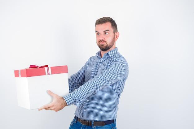 Varón joven mostrando dando gesto mientras sostiene la caja de regalo en camisa, jeans y mirando confiado, vista frontal.