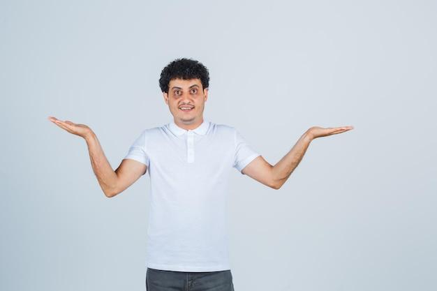 Varón joven mostrando gesto de bienvenida en camiseta blanca, pantalón y mirando confiado. vista frontal.