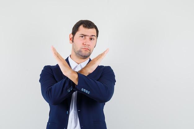 Varón joven mostrando gesto de parada en camisa, chaqueta y mirando serio