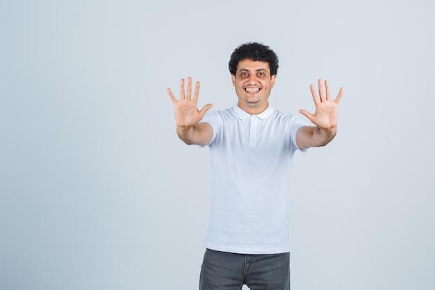 Varón joven mostrando gesto de parada en camiseta blanca, pantalones y mirando feliz. vista frontal.