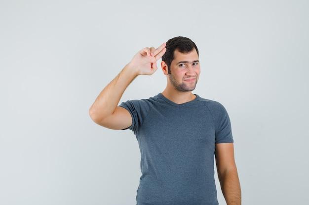 Varón joven mostrando gesto de saludo en camiseta gris y mirando confiado