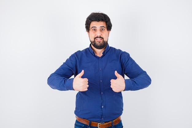 Varón joven mostrando pulgares arriba en camisa, jeans y mirando feliz, vista frontal.