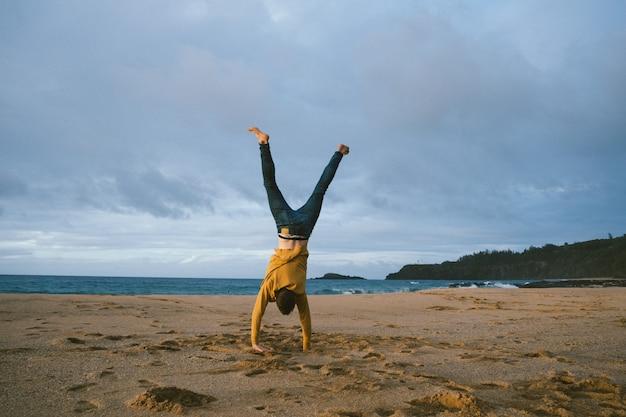 Varón joven de pie sobre sus brazos en la playa de arena en un día soleado