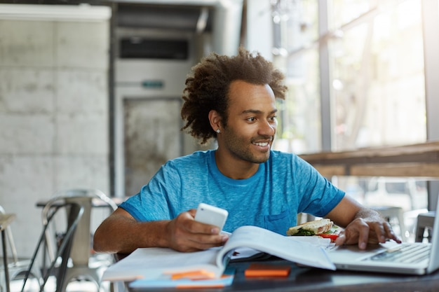 Varón joven con piel oscura y cabello rizado rodeado de libros con teléfono en la mano mirando en la computadora portátil con una sonrisa feliz de encontrar lo que necesita para el proyecto. gente, juventud, educación