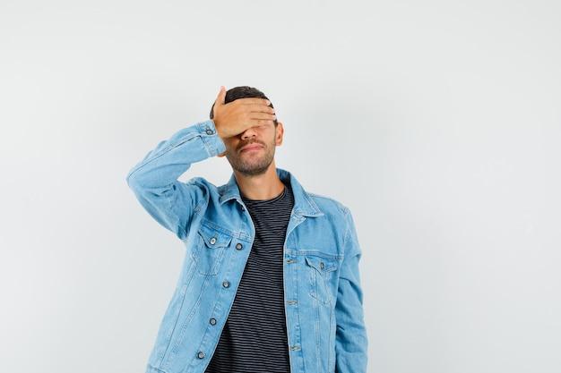 Varón joven que cubre los ojos con la mano en la chaqueta de la camiseta y parece emocionado