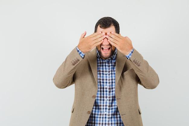 Varón joven que cubre los ojos con las manos en camisa, chaqueta y mirando emocionado, vista frontal.