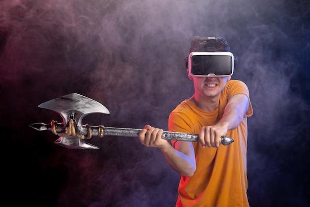 Varón joven que juega al juego de vikingo en la superficie oscura de la realidad virtual