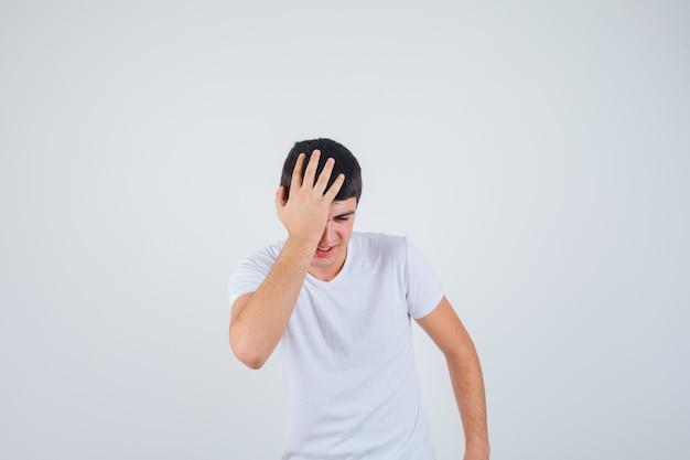 Varón joven que lleva a cabo la mano en la cabeza en camiseta y que mira feliz. vista frontal.