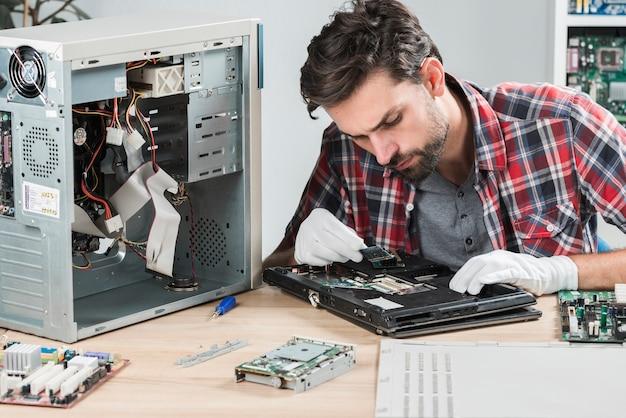 Varón joven que mira el ordenador portátil ram en el escritorio de madera