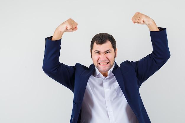 Varón joven que muestra el gesto del ganador en camisa y chaqueta y mirando dichoso