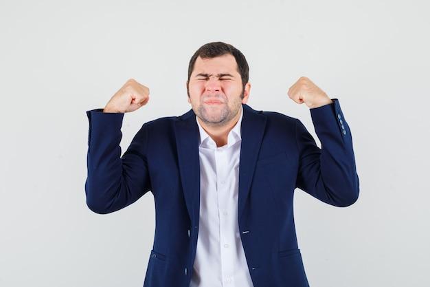 Varón joven que muestra el gesto del ganador en camisa y chaqueta y parece feliz