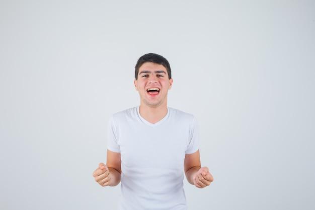 Varón joven que muestra el gesto del ganador en camiseta y parece afortunado. vista frontal.