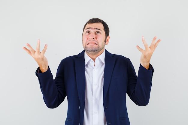 Varón joven que muestra un gesto de impotencia en camisa y chaqueta y parece confundido
