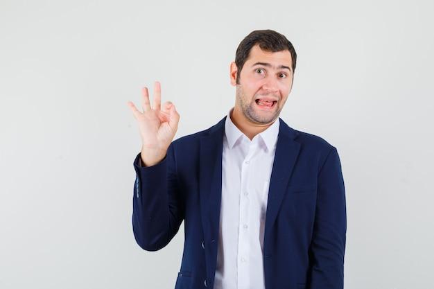 Varón joven que muestra un gesto de ok en camisa y chaqueta y parece seguro