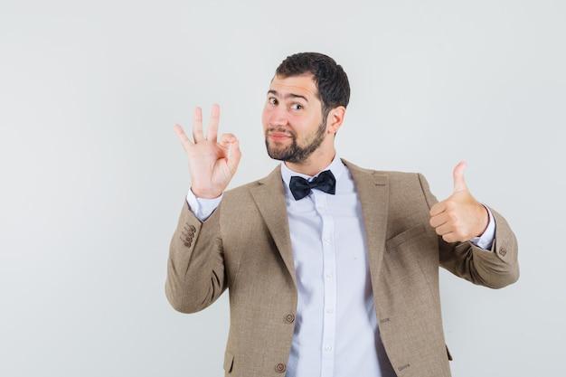Varón joven que muestra la muestra aceptable y el pulgar hacia arriba en traje y parece contento. vista frontal.