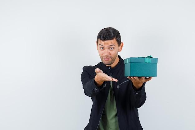 Varón joven que ofrece caja de regalo en camiseta, chaqueta y mirando alegre, vista frontal.