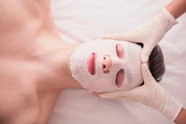 Varón joven que recibe la máscara facial en el salón de belleza.