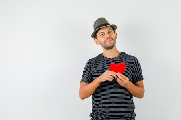 Varón joven que sostiene el corazón rojo en el sombrero de la camiseta y que parece alegre