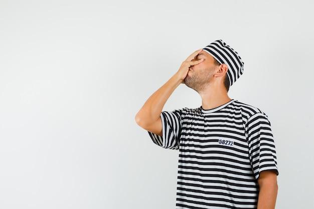 Varón joven que sostiene la mano en la cara en el sombrero de la camiseta rayada y que parece olvidadizo
