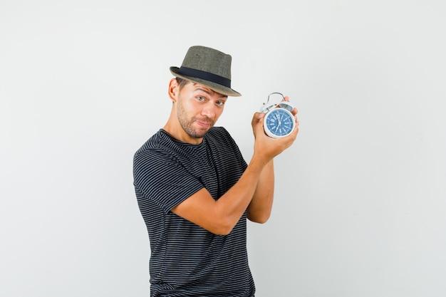 Varón joven que sostiene el reloj de alarma en el sombrero de la camiseta y que mira alegre