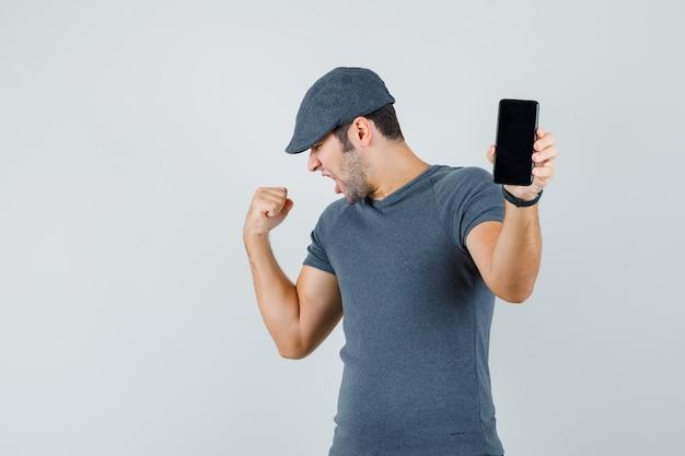 Varón joven que sostiene el teléfono móvil en la gorra de la camiseta y parece afortunado