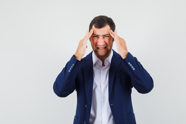 Varón joven que sufre de dolor de cabeza en camisa, chaqueta y con aspecto cansado