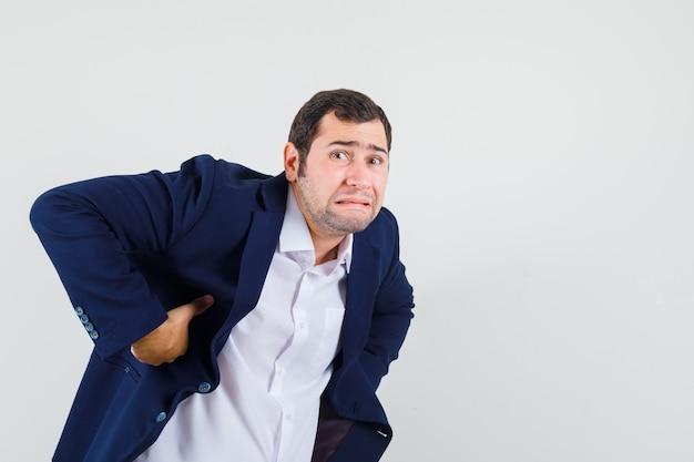 Varón joven que sufre de dolor de espalda en camisa, chaqueta y aspecto fatigado