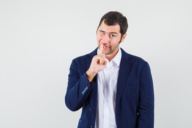 Varón joven recogiendo su nariz en camisa, chaqueta y mirando divertido