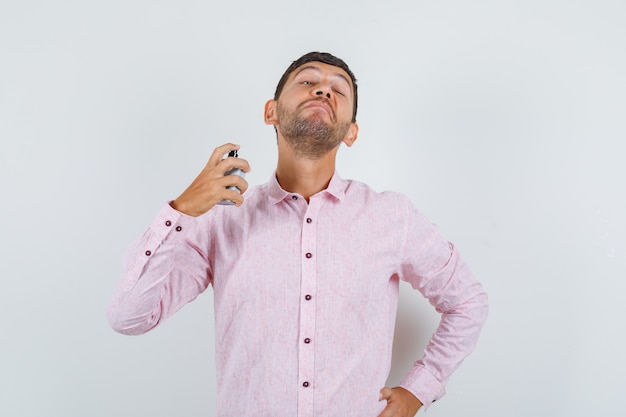 Varón joven rociar perfume en vista frontal de la camisa rosa.