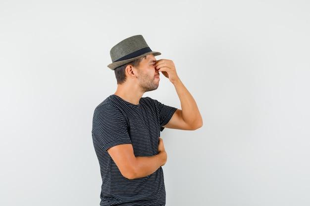 Varón joven con sombrero de camiseta frotándose los ojos y la nariz y mirando agotado