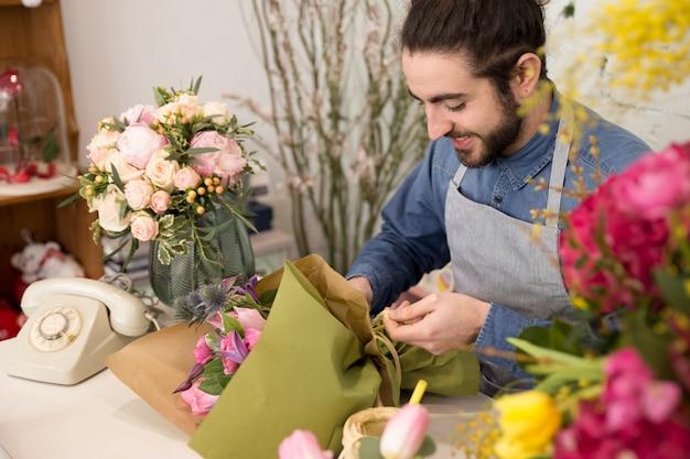 Varón joven sonriente que envuelve el ramo de la flor en floristería