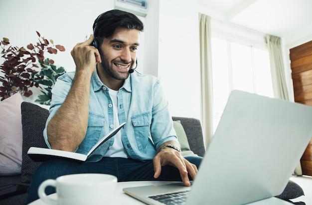 Varón joven sonriente en su computadora portátil al personal del operador del centro de llamadas hablando con los clientes a través de auriculares