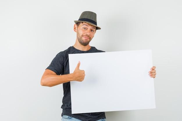 Varón joven sosteniendo el lienzo en blanco mostrando el pulgar hacia arriba en el sombrero de los pantalones vaqueros de la camiseta y mirando contento