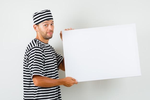 Varón joven sosteniendo un lienzo en blanco con un sombrero de camiseta a rayas y mirando alegre