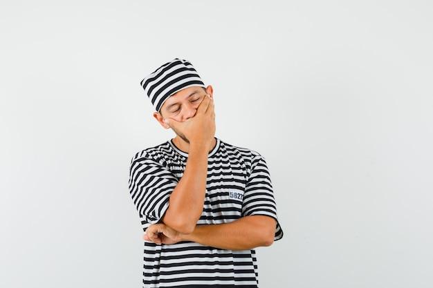 Varón joven sosteniendo la mano en la boca con sombrero de camiseta a rayas y mirando soñoliento