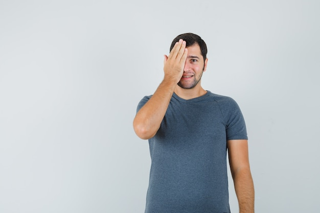 Varón joven sosteniendo la mano en un ojo en camiseta gris y mirando positivo
