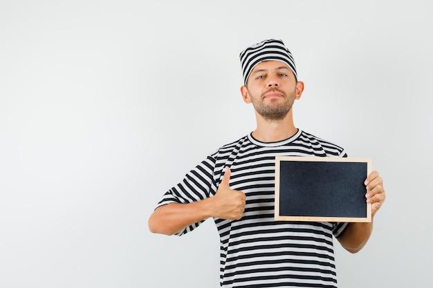 Varón joven sosteniendo la pizarra mostrando el pulgar hacia arriba con sombrero de camiseta a rayas y mirando confiado