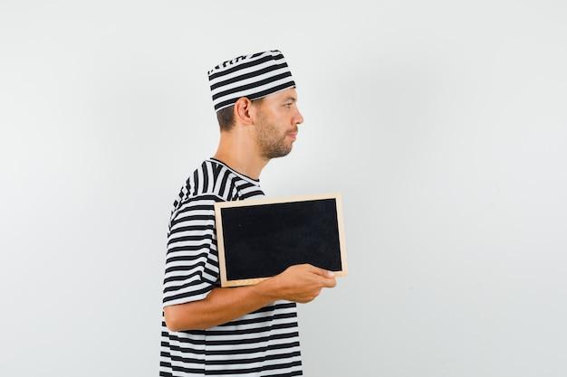 Varón joven sosteniendo la pizarra en el sombrero de camiseta a rayas y mirando tranquilo