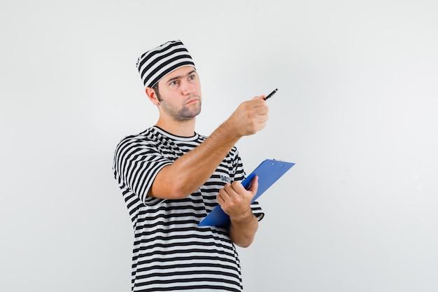 Varón joven sosteniendo portapapeles, bolígrafo, apuntando hacia afuera en camiseta, sombrero y mirando pensativo, vista frontal.