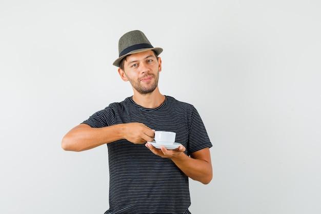 Varón joven sosteniendo una taza de café con sombrero de camiseta y mirando alegre