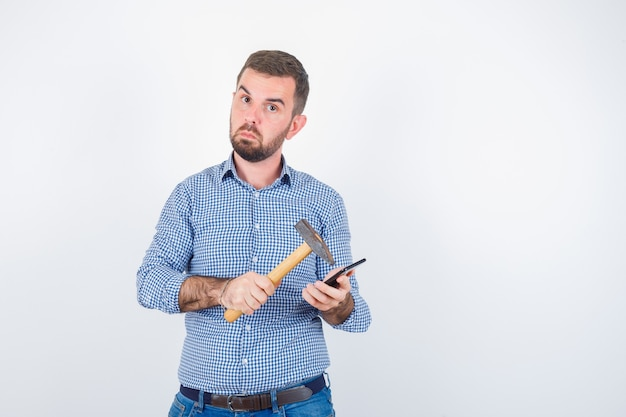 Varón joven teléfono móvil llamativo con un martillo en camisa, jeans y mirando vacilante, vista frontal.