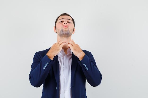 Varón joven tirando del cuello de su camisa en camisa y chaqueta y mirando orgulloso