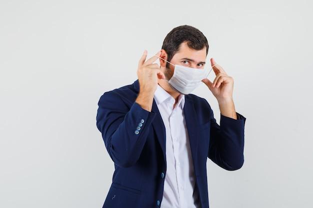 Varón joven vistiendo máscara médica en camisa