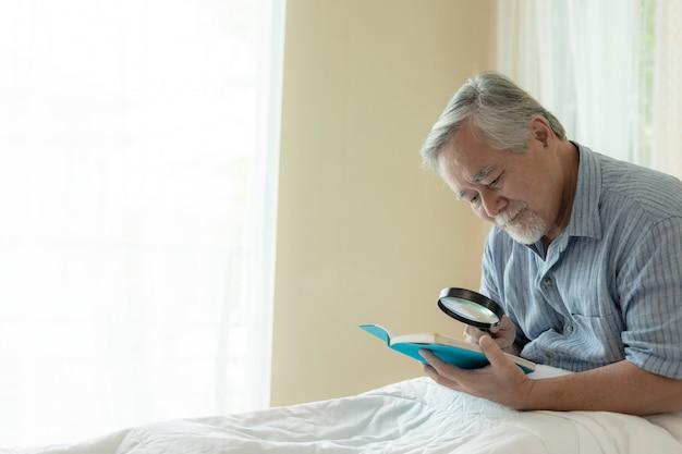 Varón mayor que lee un libro, sensación feliz de la sonrisa en cama en casa - concepto del mayor de la forma de vida