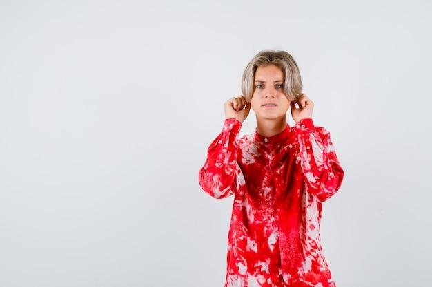 Varón rubio adolescente en camisa de gran tamaño tirando de los lóbulos de las orejas hacia abajo y mirando furioso