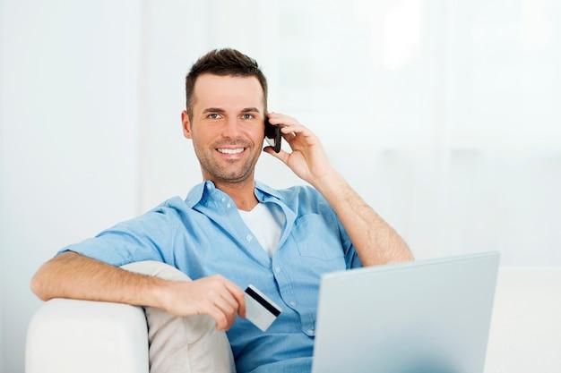Varón sonriente de compras a través de internet