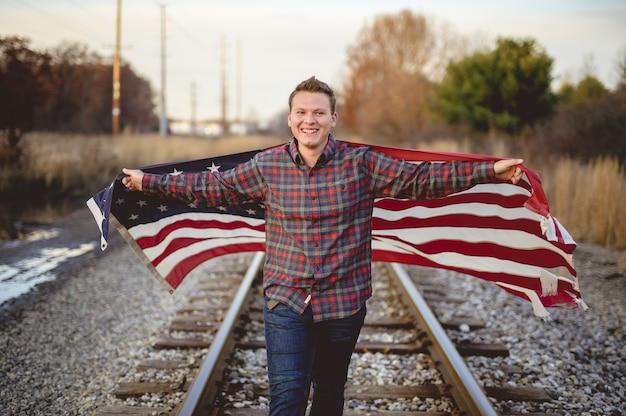 Varón sonriente sosteniendo la bandera de los estados unidos mientras camina sobre los rieles del tren