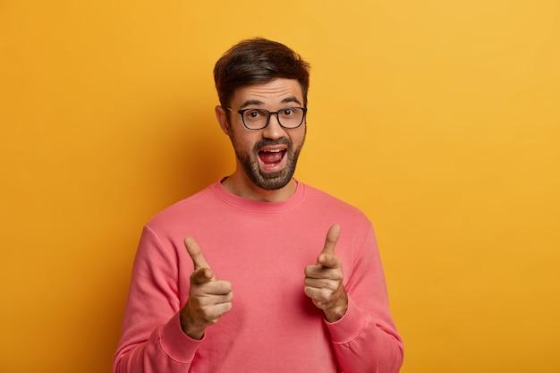 Vas conmigo. juguetón y positivo hombre sin afeitar da la bienvenida a un amigo y saluda, señala con un gesto de pistola, saluda o felicita a la persona, usa un jersey informal, posa sobre una pared amarilla