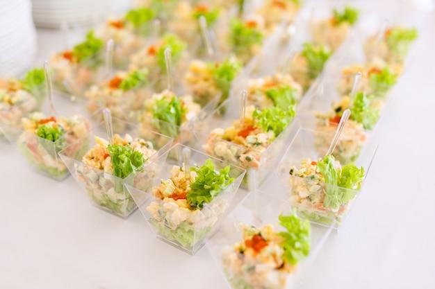 Vasitos con ensaladas frescas, huevos, salmón y pepinos de pie sobre la mesa blanca